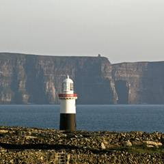 Lighthouse on Inisheer looking over to the Cliffs of Moher