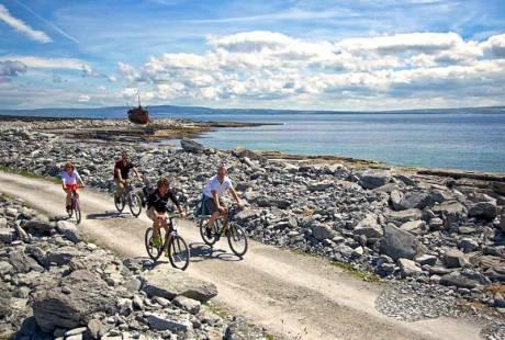 People riding bikes on Aran Islands by Plassey Shipwreck